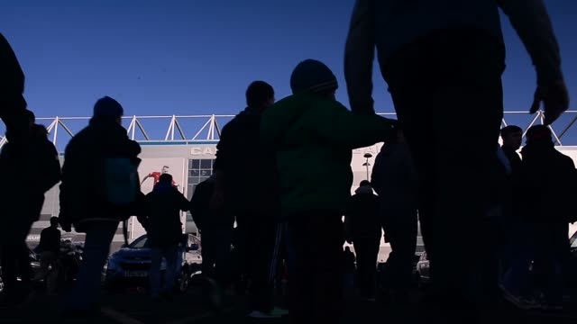 Low Angle Mid Shot people gathering in front of stadium Cardiff City FC Football Club shot ahead of a match on the 23rd of November 2013 in Cardiff...