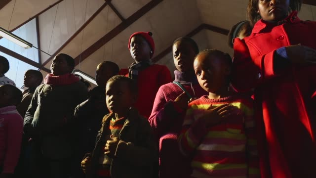 low angle mid shot the congregation prays during a sunday service at regina mundi church in soweto on june 16 2013 in johannesburg south africa youth... - sonntag stock-videos und b-roll-filmmaterial