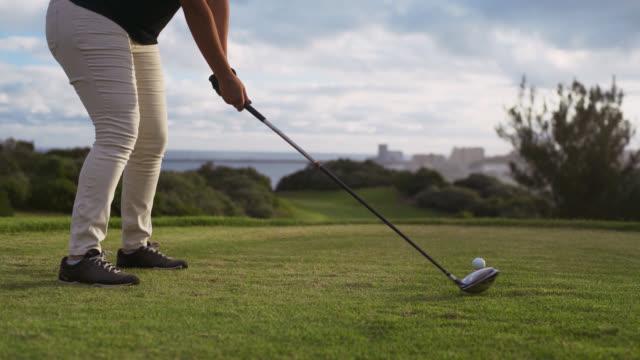 low angle midshot of a woman hitting a golf ball - golfgreen bildbanksvideor och videomaterial från bakom kulisserna