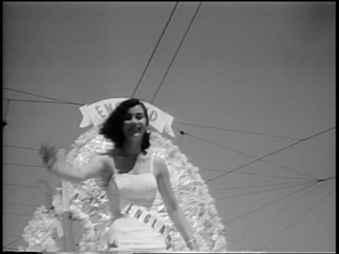 B/W 1956 low angle Miss England waving from float in Miss Universe beauty parade / Long Beach CA / news