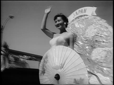 vídeos y material grabado en eventos de stock de b/w 1956 low angle pan miss japan waving from float in miss universe beauty parade / long beach ca - traje de baño de una pieza