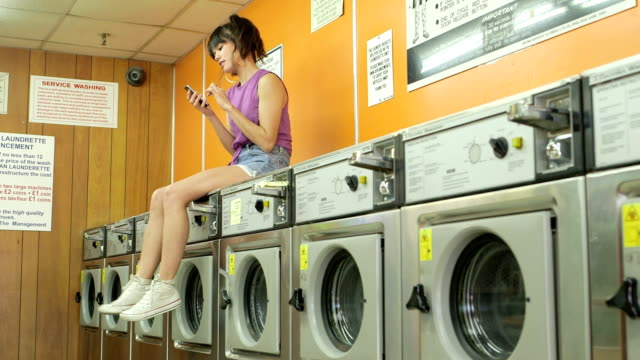 low angle mls a young woman sits waitng in a launderette - waschsalon stock-videos und b-roll-filmmaterial