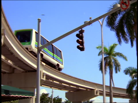 low angle pan monorail car travelling on miami metrorail track above traffic light / miami, florida - travelling light stock videos & royalty-free footage