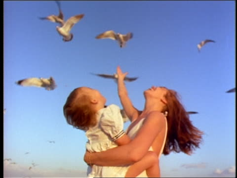low angle mother holding little girl in sailor suit + spinning as seagulls fly overhead on windy day - sailor suit stock videos and b-roll footage