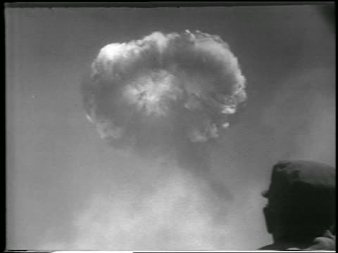 B/W 1952 low angle mushroom cloud from Hbomb explosion / soldier's head in foreground / Yucca Flats Nevada
