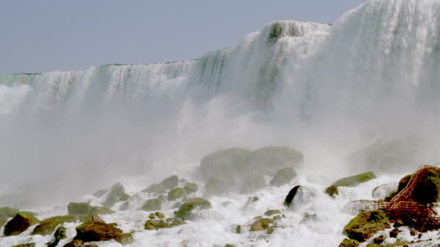 low angle pan niagara falls with mist rising at bottom / rocks in foreground - naturwunder stock-videos und b-roll-filmmaterial