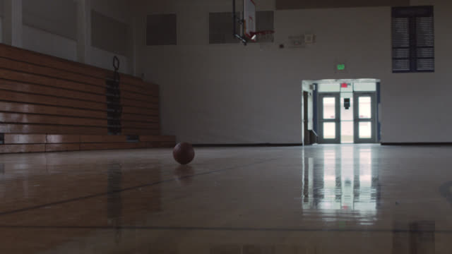 vídeos de stock, filmes e b-roll de low angle of a basketball sitting in an empty school gym. - quadra esportiva