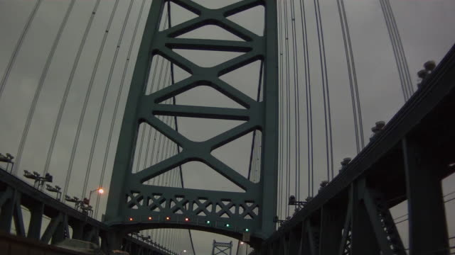 pov low angle of a vehicle traveling across a large urban suspension bridge into a large city with an overcast sky. - philadelphia pennsylvania stock videos & royalty-free footage