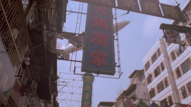 low angle of airliner flying low over buildings and signs / kowloon / kai tek, hong kong - 1997 stock-videos und b-roll-filmmaterial
