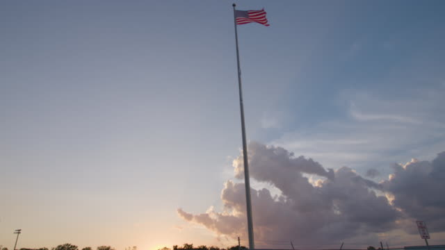 Low angle of American flag high on pole during sunset