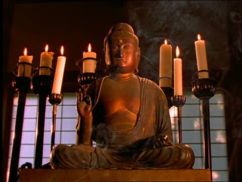 low angle of amida buddha statue with candles / incense smoke in foreground - männliche figur stock-videos und b-roll-filmmaterial