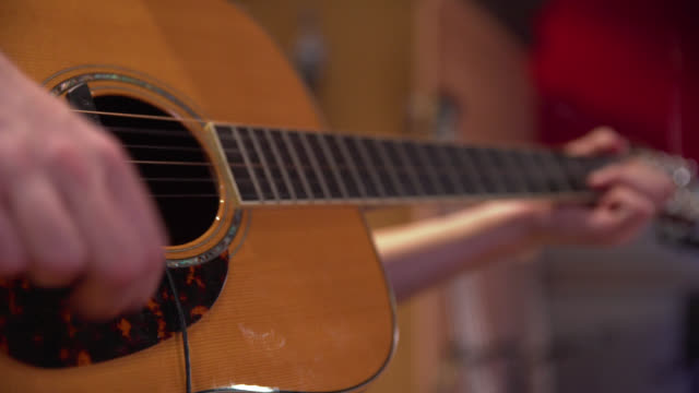 low angle of an acoustic guitar being strummed - guitar stock videos & royalty-free footage