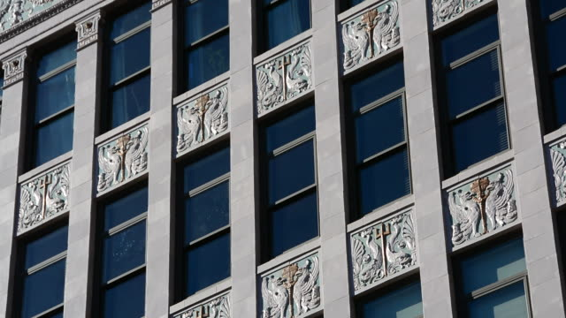 vidéos et rushes de low angle of art deco style building facade pan to ornate fire escape - en dernier