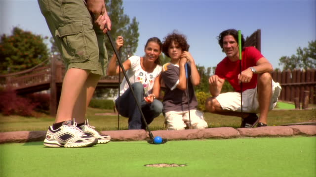 low angle of boy putting on mini golf course with family members kneeling to watch / family members raising arms in celebration after ball goes into hole / boy removing ball - minigolf stock-videos und b-roll-filmmaterial
