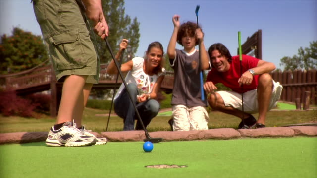 Low angle of boy putting on mini golf course with family members kneeling to watch / family watching in anticipation as ball rolls toward hole / boy falling onto green in disappointment as ball rolls past hole