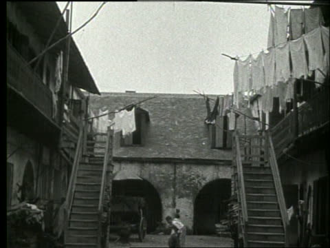 b/w low angle of clotheslines and stairs to bldgs / children below / 1915 new orleans / no sound - 1915年点の映像素材/bロール