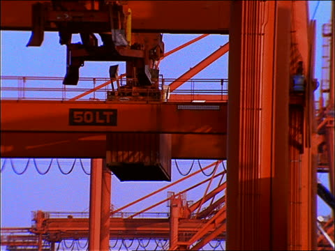 low angle of crane loading container onto ship at port / seattle - seattle stock videos & royalty-free footage