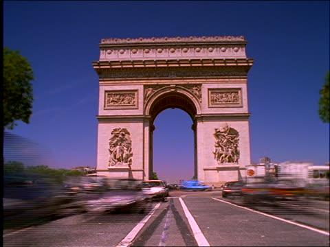vidéos et rushes de low angle of heavy time lapse traffic in front of arc de triomphe /paris - arc élément architectural