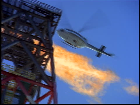 low angle of helicopter flying over tower with fire on offshore oil rig / Brazil