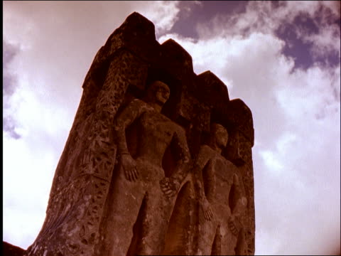 low angle of human figures in monolithic burial stone of king / clouds in background / Sumba / Indonesia