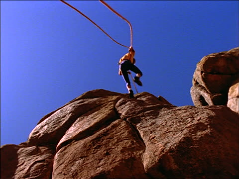low angle of male rock climber rappelling down side of rocks