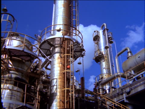 vidéos et rushes de low angle of man climbing up ladder at oil refinery / brazil - 1997
