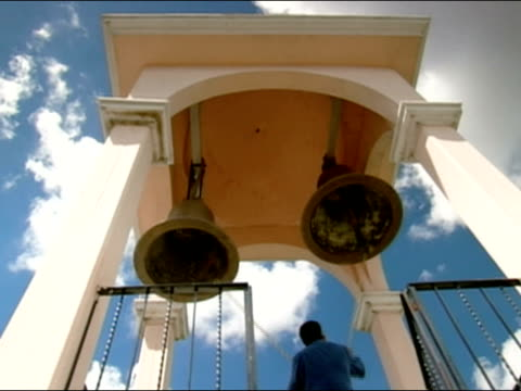 low angle of man ringing bells in tower of church / puebla, mexico - bell stock videos & royalty-free footage
