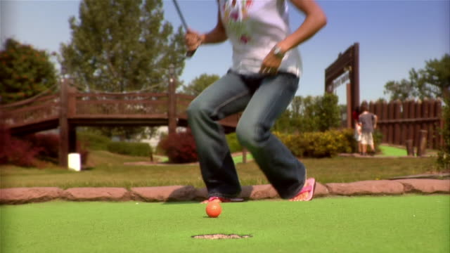 low angle of orange golf ball on putting green at mini golf course / woman walking up to ball and kneeling on green / using golf club like pool stick to hit ball into hole / raising arms in celebration / removing ball - golf video stock e b–roll