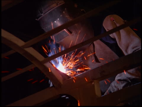 low angle of person in helmet welding metal structure / brazil - steel worker stock videos & royalty-free footage
