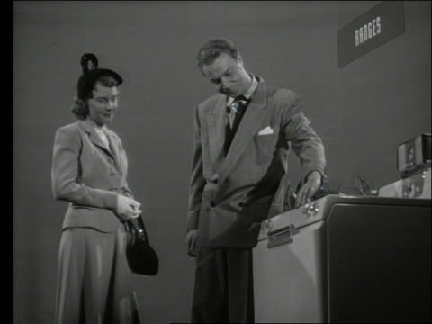 b/w low angle of salesman showing stove to woman in store - consumerism stock videos and b-roll footage