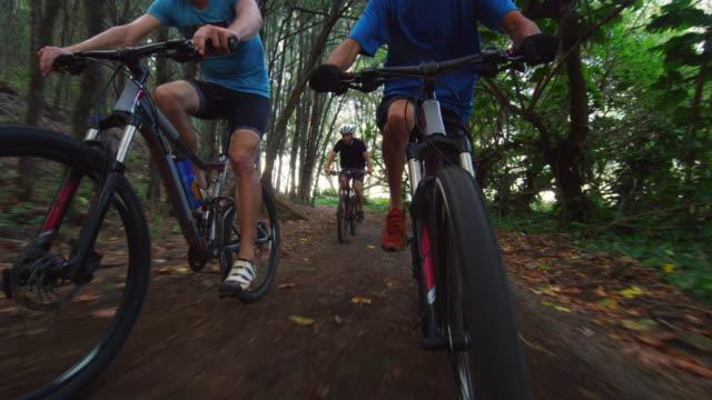 low angle of three men racing on mountain bikes through woods - タートル湾点の映像素材/bロール