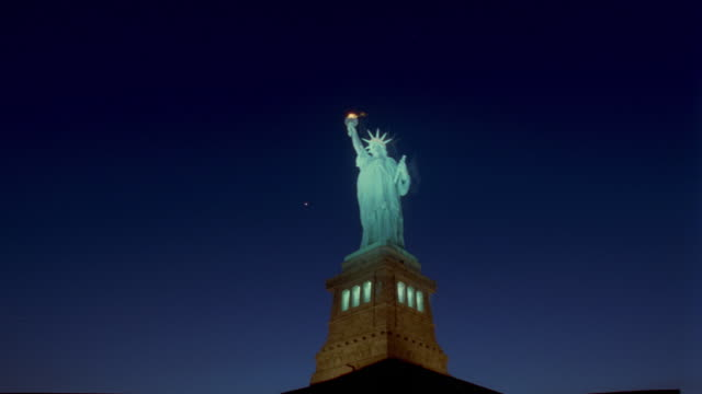 low angle of time lapse statue of liberty at night / new york city - statue of liberty stock videos & royalty-free footage