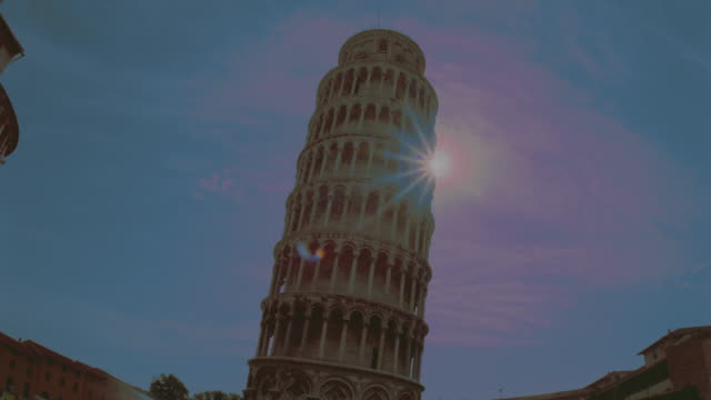 low angle of time lapse sunrise behind Tower of Pisa / Italy