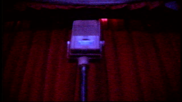 Low Angle of Vintage Microphone on Stand with Stage Curtains Opening and Closing Behind in Clear Lake Wisconsin