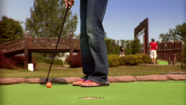 low angle of woman wearing flip-flops putting on mini golf course / jumping up and down after ball goes into hole - holing stock videos & royalty-free footage