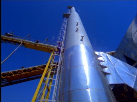 low angle pan of oil refinery storage tanks / worker climbing ladder / brazil - 1997年点の映像素材/bロール