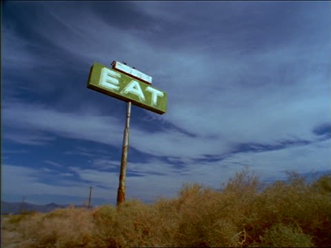 low angle old roadside diner 'Eat' sign with blue sky in background / Owens Valley, California