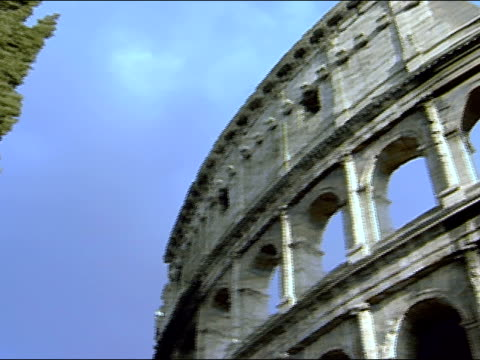 Low angle pan from tree to exterior of Coliseum / Rome, Italy
