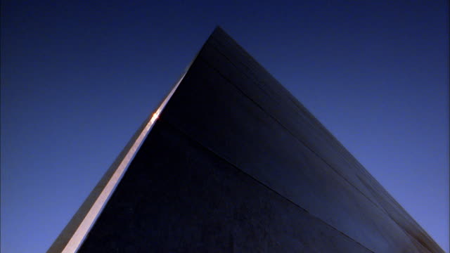 Low angle pan Gateway Arch w/blue sky in background / St. Louis