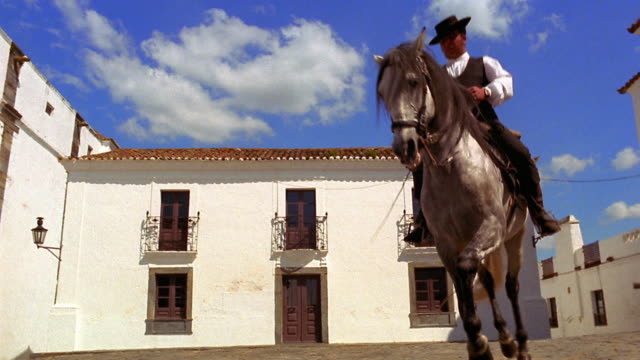 Low angle pan man on Lusitano horse doing dance-like movements (dressage) / church background / Monsaraz, Portugal