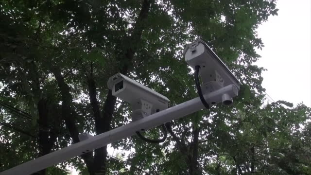 low angle pan shot of a surveillance camera set on a pole above a street in urumqi uyghur - xinjiang province stock videos & royalty-free footage