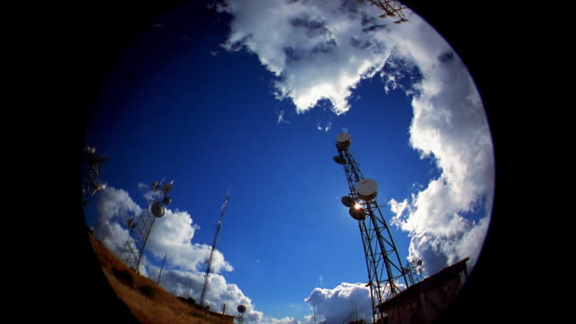 low angle pan time lapse clouds passing over broadcast towers - microwave tower stock videos and b-roll footage