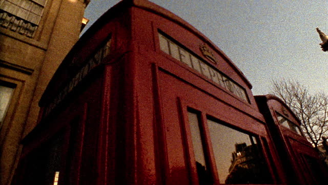 low angle pan two red telephone booths with nelson's column and trafalgar square in background / london, england - nelson's column stock videos and b-roll footage