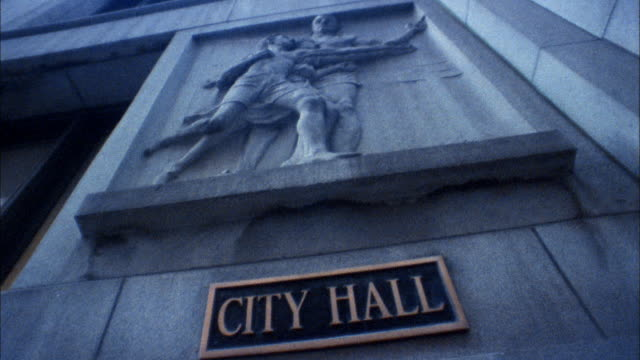 Low angle pan view of sculpture and sign on exterior wall of City Hall / Chicago