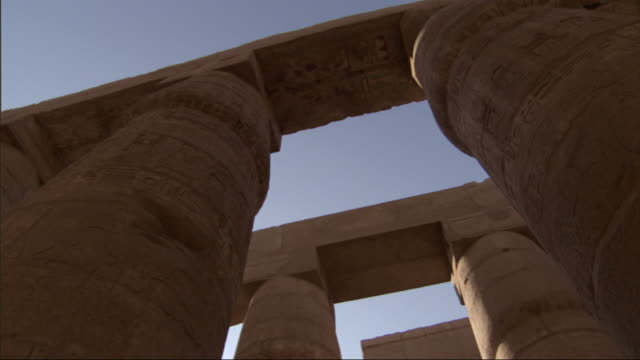 Low Angle, pan-left - Carvings of hieroglyphs cover the columns of ancient adobe buildings / Egypt