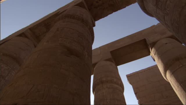low angle, pan-left - carvings of hieroglyphs cover the columns of ancient adobe buildings / egypt - adobe material stock videos and b-roll footage