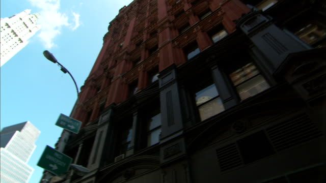 low angle pan-left - the woolworth building towers over adjacent high-rises in new york city. / new york city, new york, usa - woolworth building stock videos & royalty-free footage