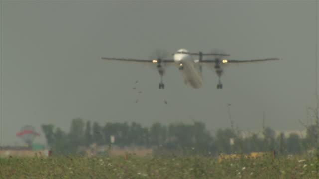 low angle pan-left tilt-up - a prop plane takes off.  - propeller bildbanksvideor och videomaterial från bakom kulisserna