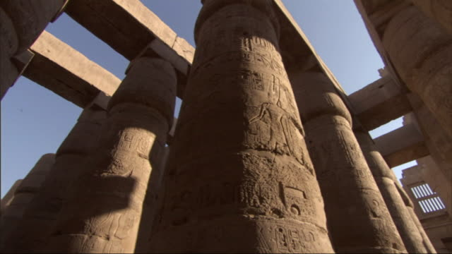 Low Angle, pan-left tracking-left - Carvings of hieroglyphs cover the columns of ancient adobe buildings / Egypt