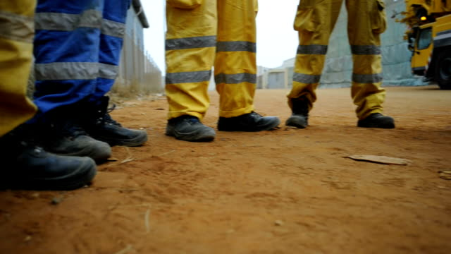 low angle panning left to right over industrial workers legs and shoes/luanda/ angola - 建設作業員点の映像素材/bロール